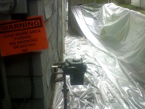 Side of home prior to painting with lead-safe signage and additional protective covering